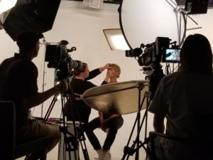 Video production team working with a model