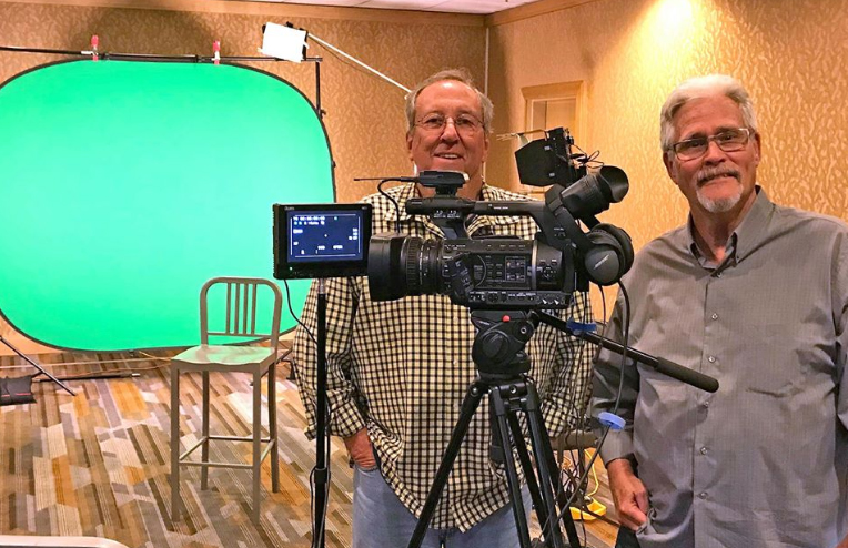 Video camera and green screen with two camera operators in San Diego hotel